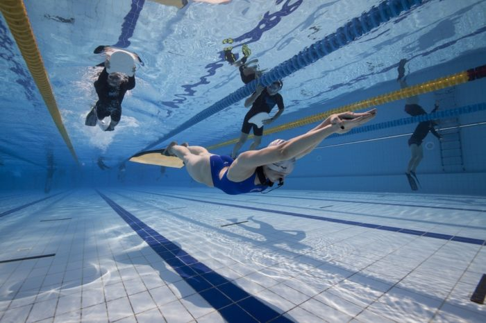 Freediver swimming in the Dynamic Pool Discipline with Safety on the surface