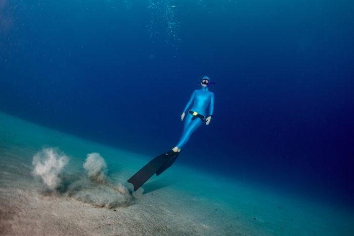 Freediving diver ascending from the sandy bottom