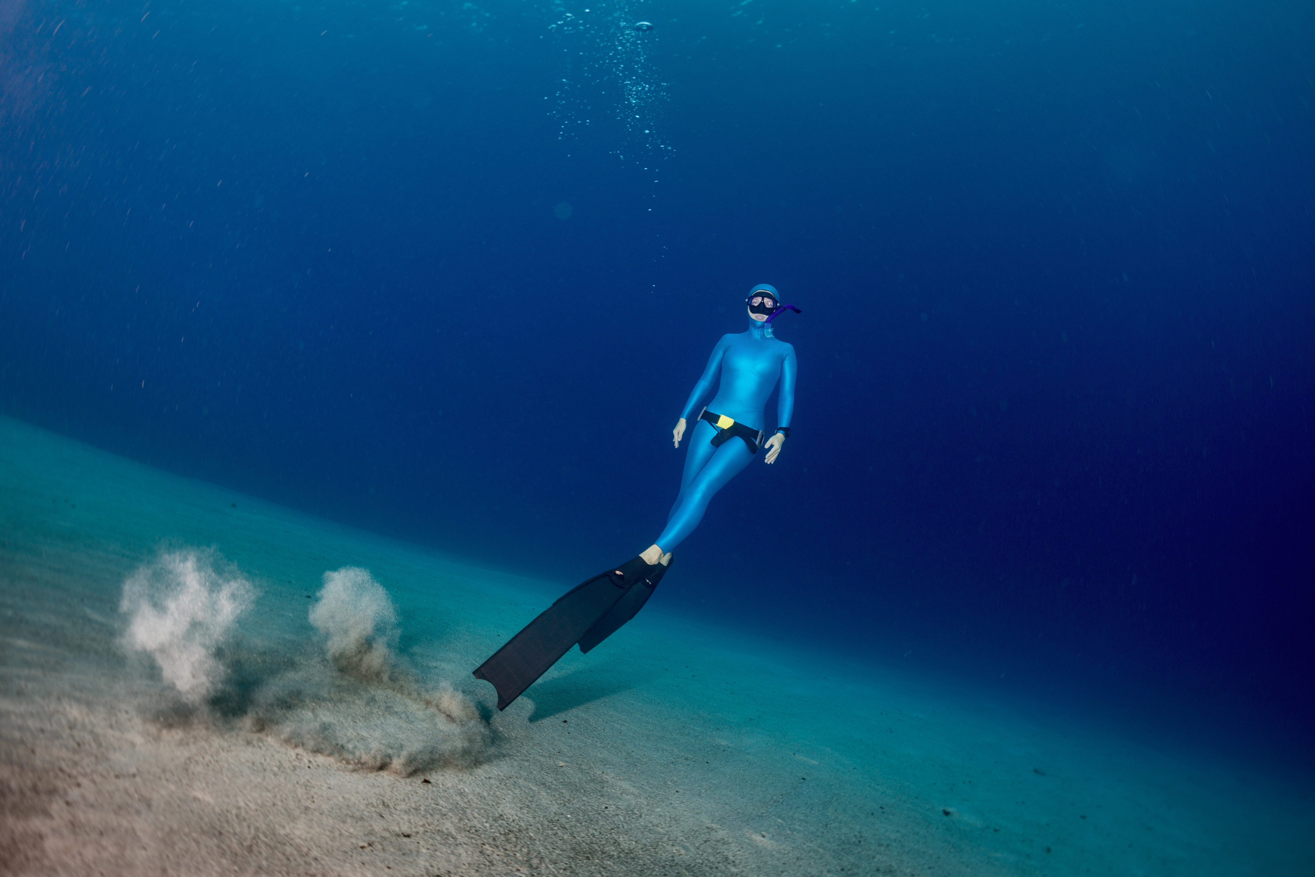 Freediving diver ascending from the sandy bottom