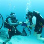 PADI Dive Instructor Bethy Driscoll congratulates T Cumming on completing his Deep Adventure Dive, Fiji 2016