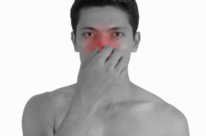 Man holding his nose because of sinus pain.