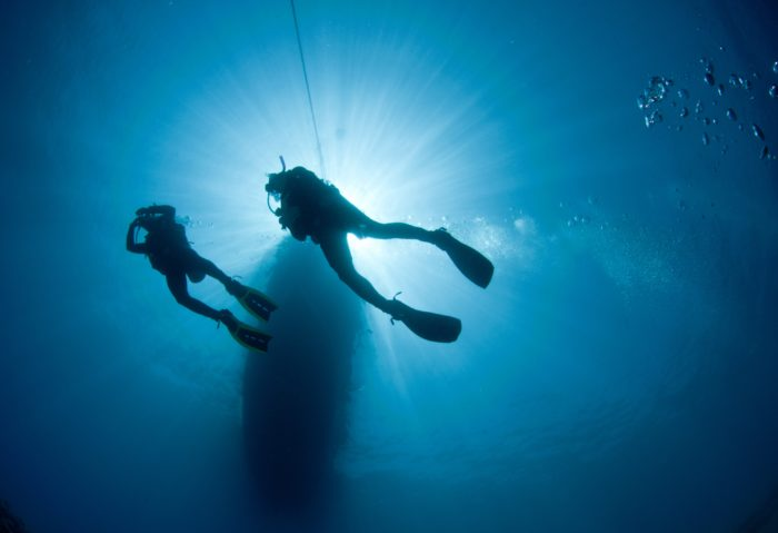 Two scuba divers are silhouetted in blue water