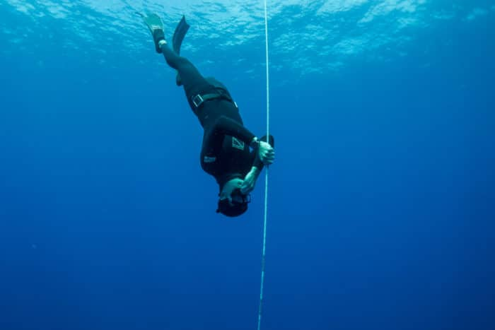 Freediver descending down a line and equalizing (Photo: Immersion Freediving)