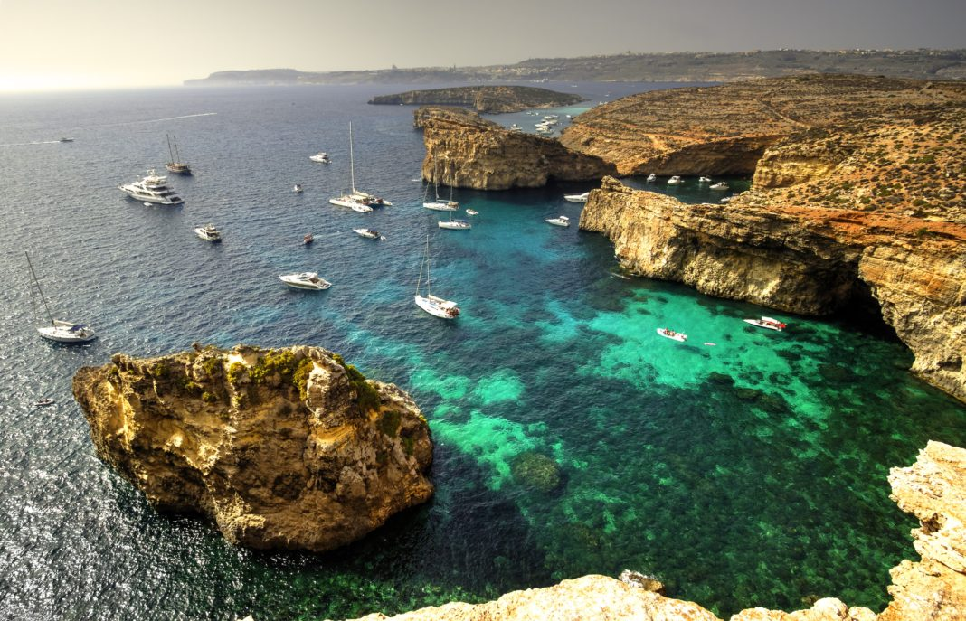 Yachts and leisure boats moored on the blue lagoon of Comino Island, Malta.