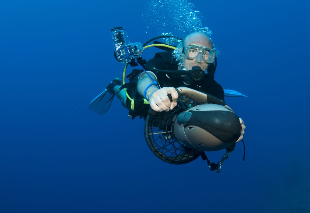 Scuba Diver plays on underwater scooter / diver propulsion vehicle