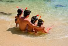 Happy family snorkeling and having fun on beach vacation