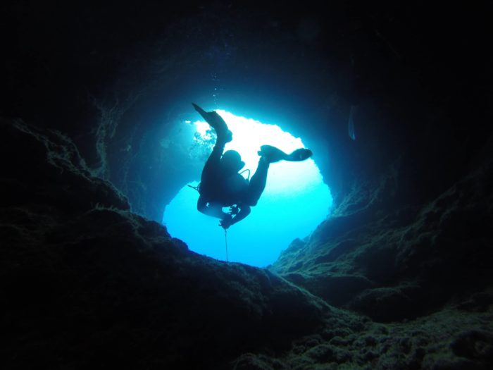 A scuba diver swimming through one of the caverns at Yap Caverns Dive Site.
