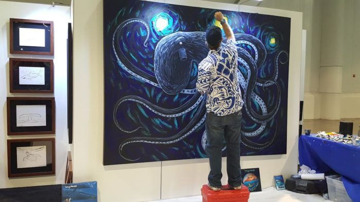 Wyland painting a canvas at DEMA Show 2016
