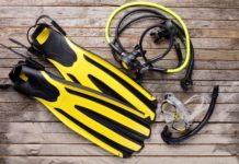 Mask, fins, regulator and snorkel on wooden desk. Equipment for diving