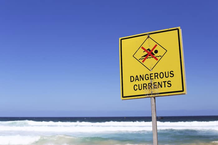 Dangerous currents sign on the beach at sunny day