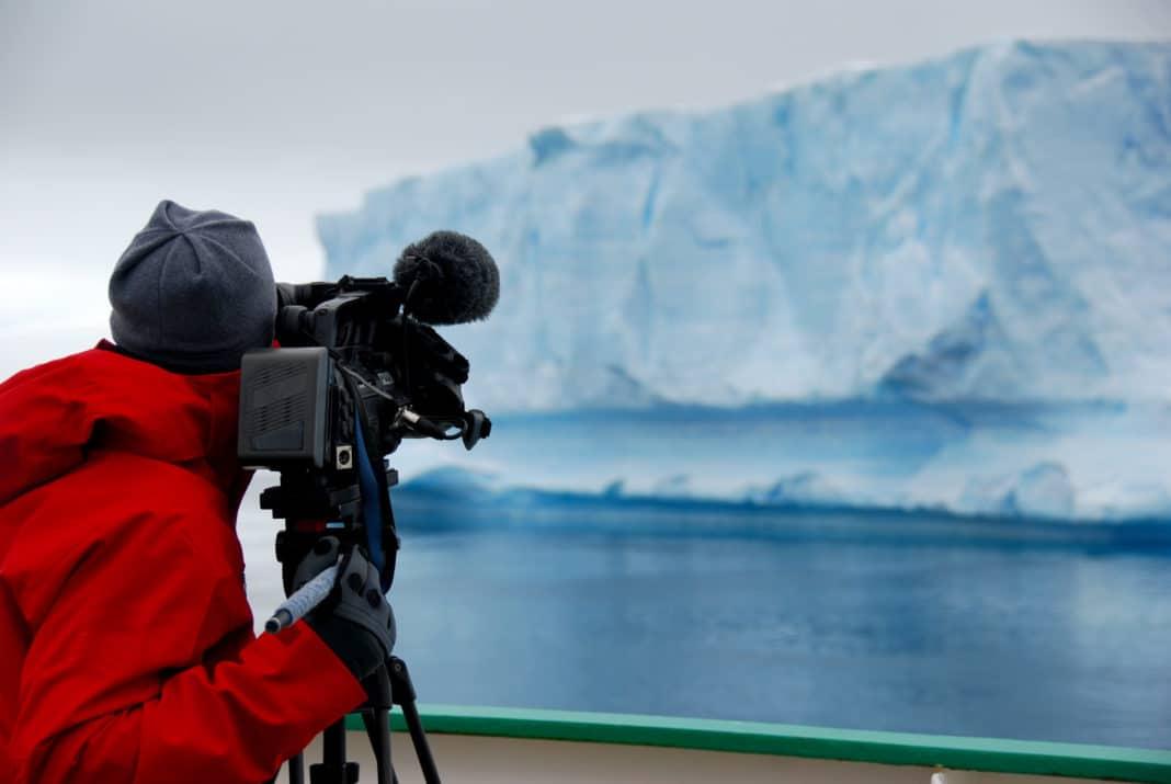 Cameraman films an iceberg in Antarctica