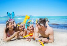 Family on the beach with snorkeling gear