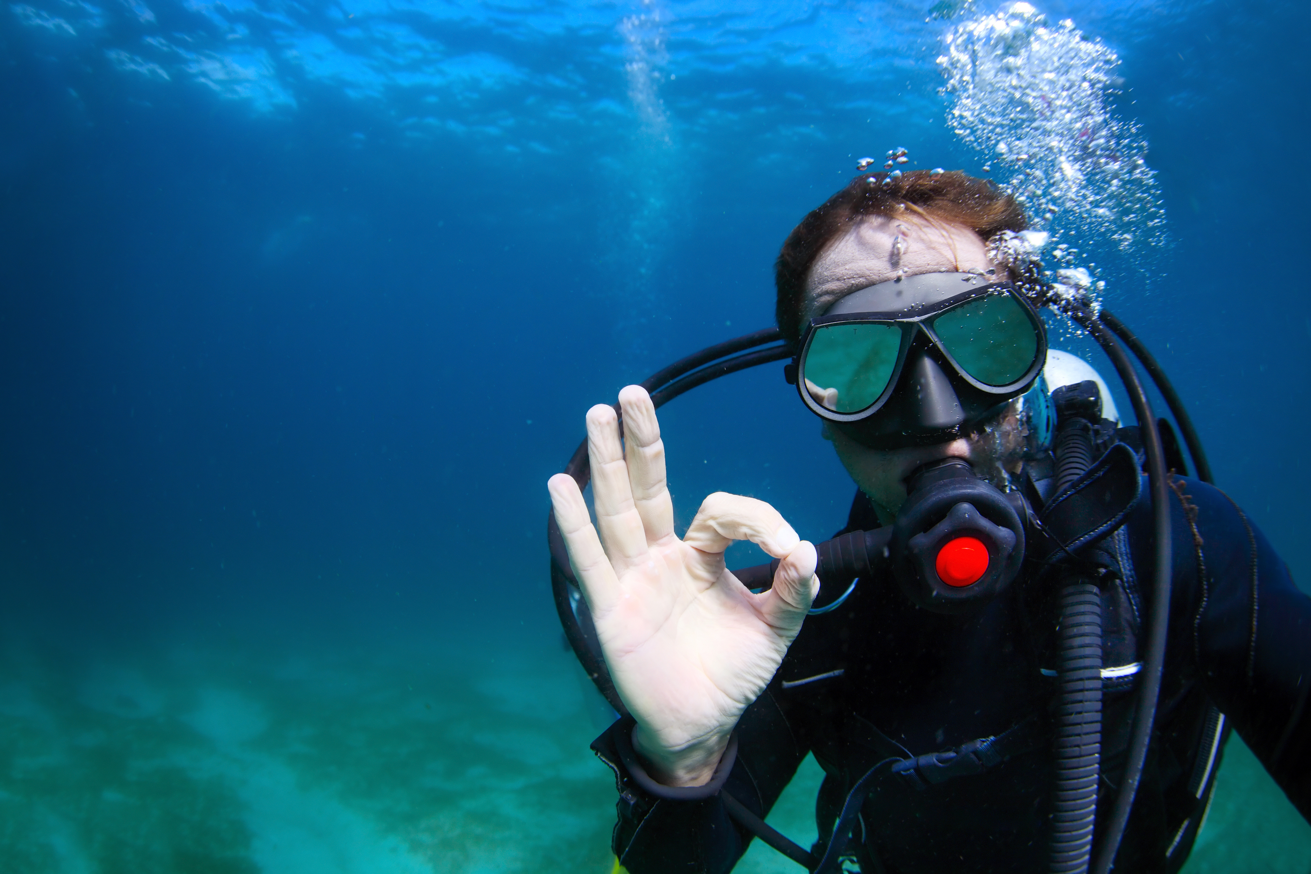 Underwater shoot of a man diving with scuba and showing ok signal