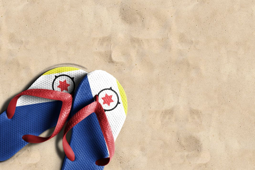 Thongs with flag of Bonaire, on beach sand