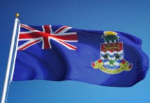 Cayman Islands flag waving against clean blue sky, close up,