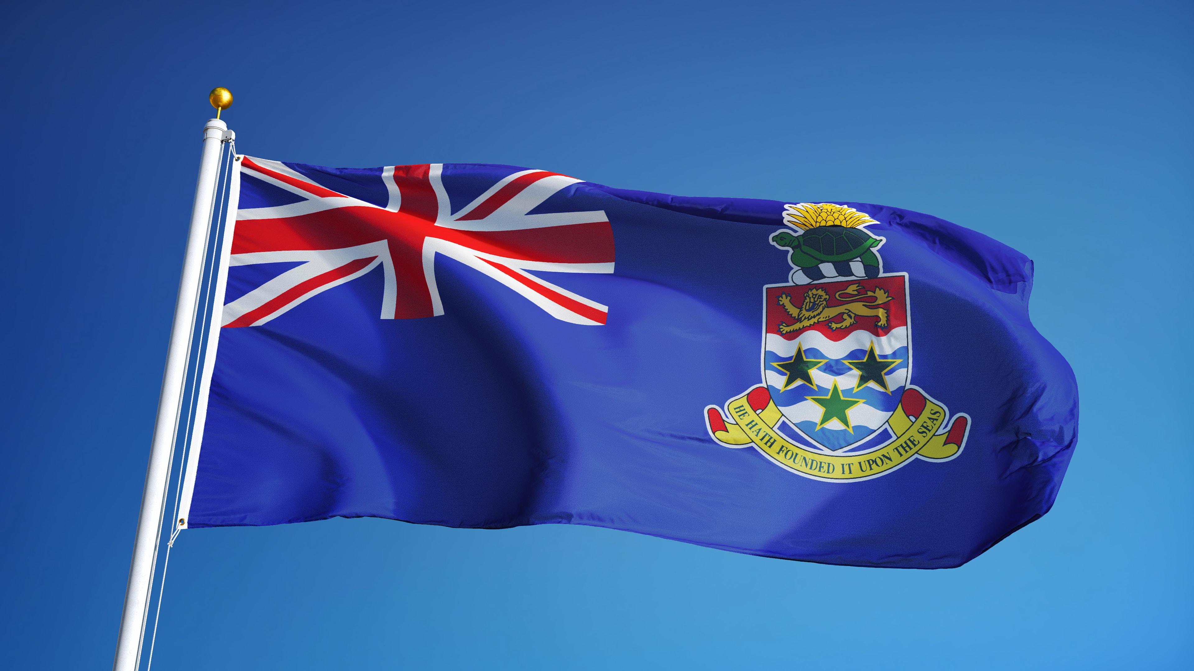 Cayman Islands flag waving against clean blue sky, close up,