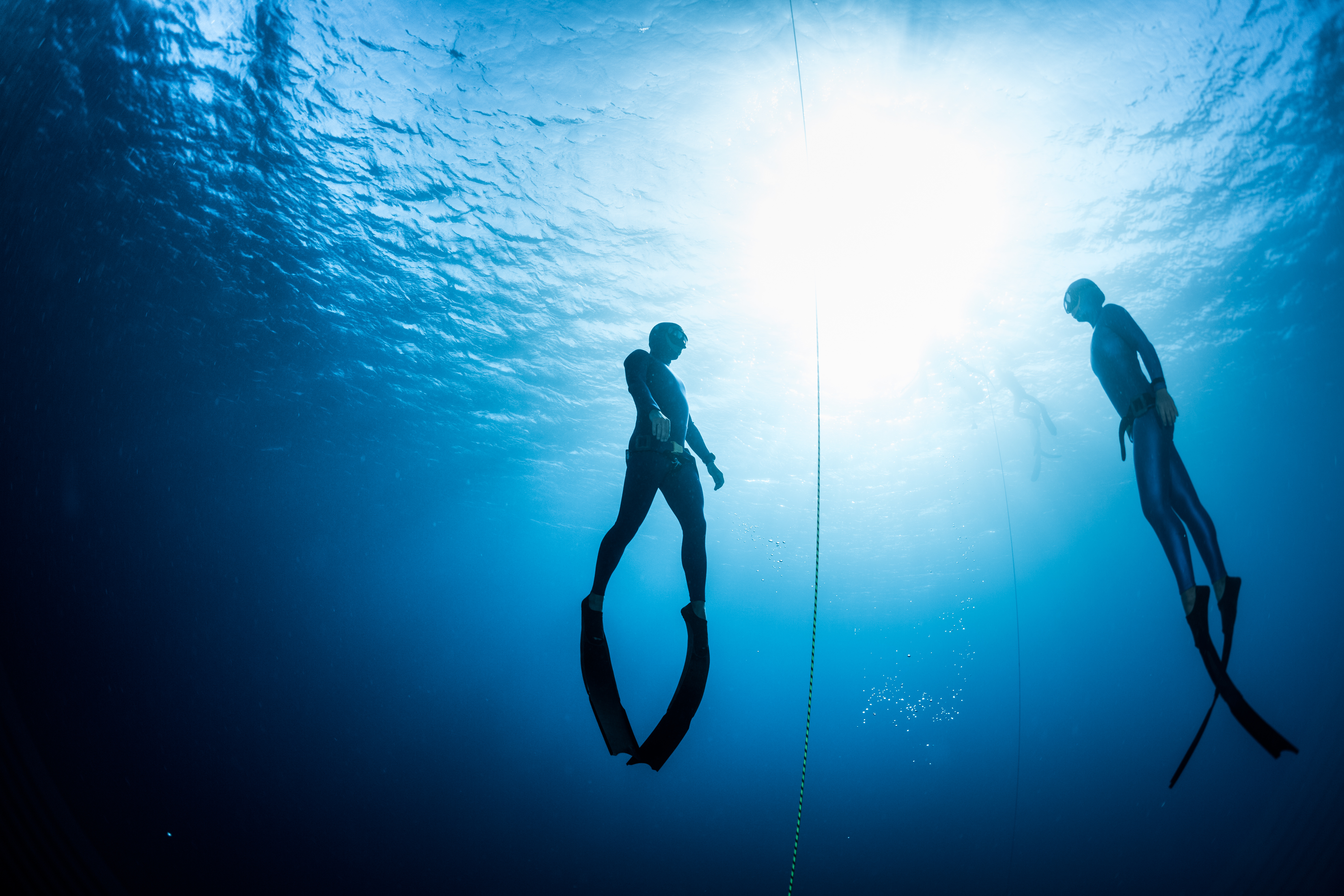 Two free divers, man and woman, ascending from the depth