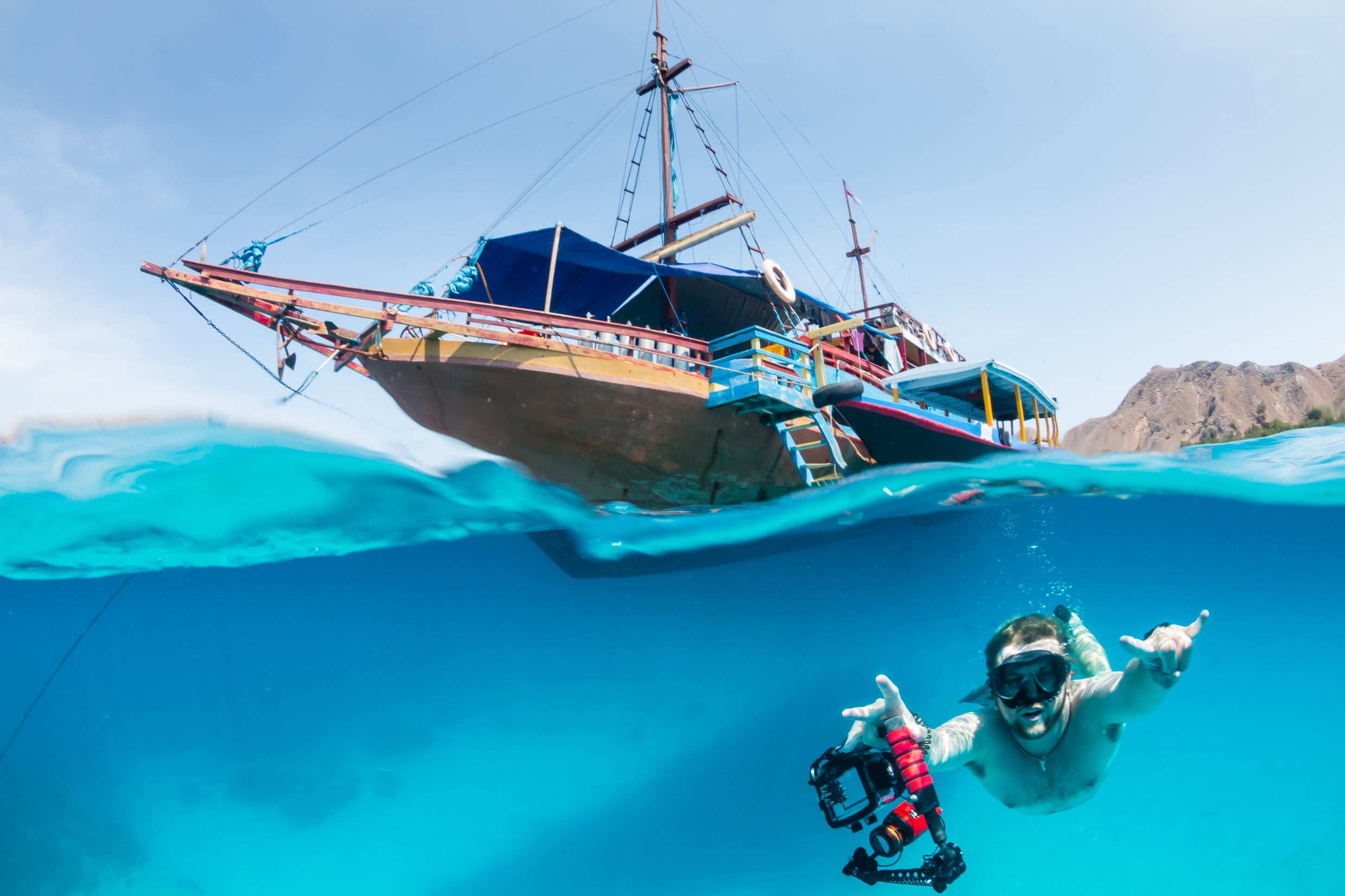 A freediver swims underwater next to a traditional boat on a tropical coral reef