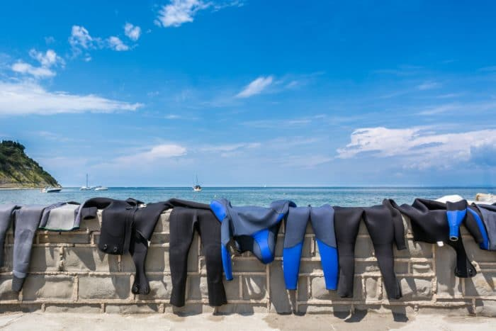 Wetsuits drying on a brick wall with a sea view