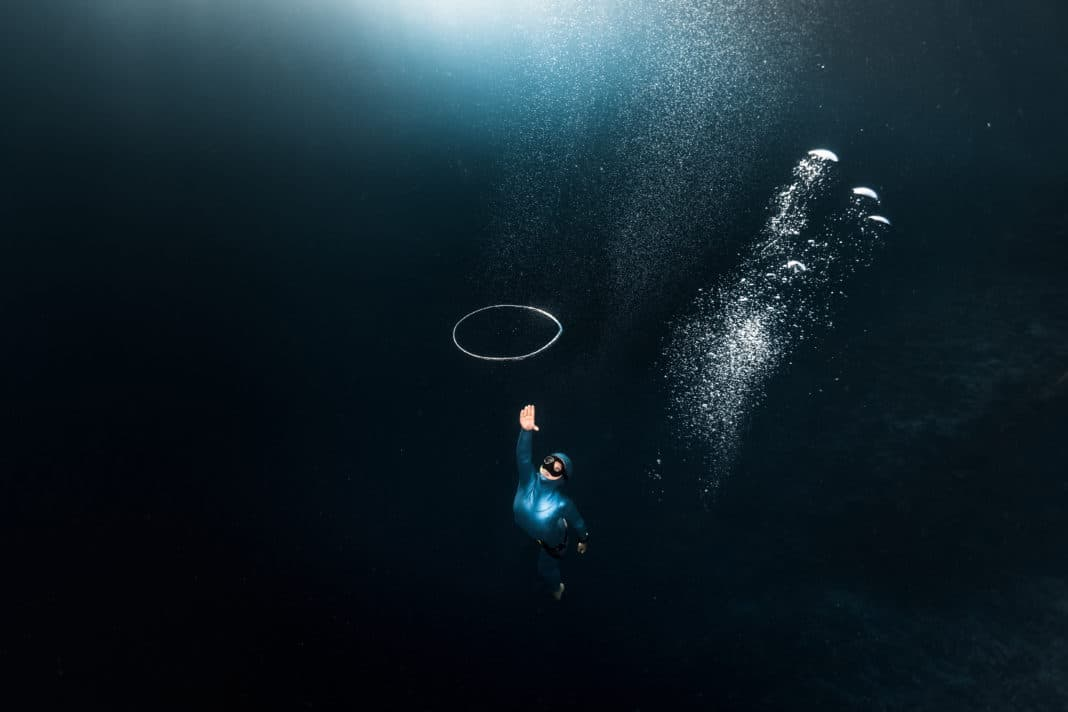 Woman free diver chases bubble ring rising from the depth