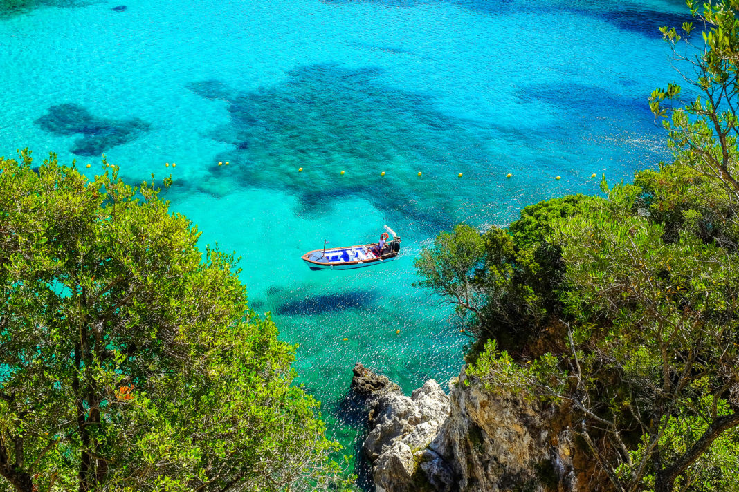 Aerial view on the boat on the crystal sea waer on the beach Paleokastritsa on the Island Corfu, Greece.