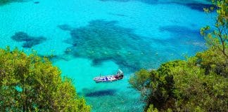 Aerial view on the boat on the crystal sea waer on the beach Paleokastritsa on the Island Corfu, Greece.