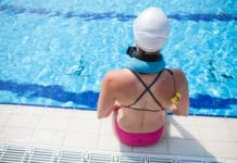 Female freediver preparing for dive at edge of outdoor swimming pool