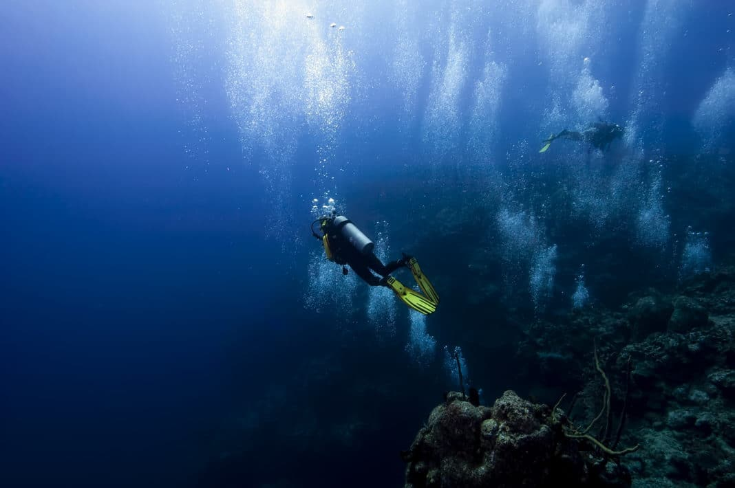 A group of divers are cruising around at the top of the 100ft drop wall in Grand cayman whilst they do a safety rest stop after a deep dive. Multitudes of bubbles are cascading upwards to the surface of the ocean.