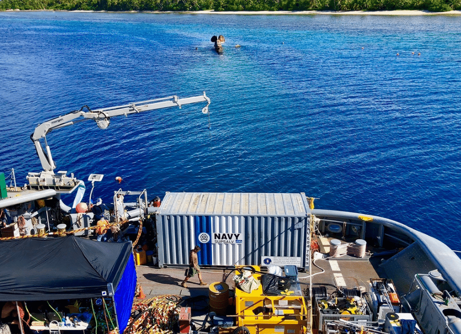 Divers and support personnel conduct recovery operations aboard the Military Sealift Command salvage ship USNS Salvor (T-ARS 52) while moored over the capsized World War II German heavy cruiser Prinz Eugen. (U.S. Navy photo)