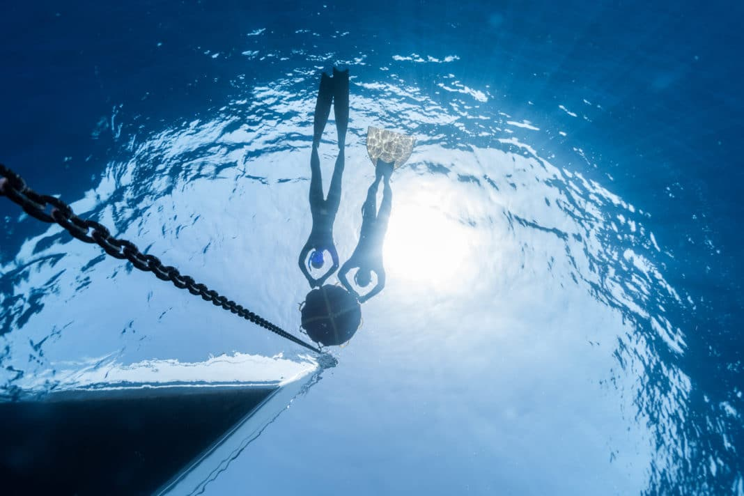 Two free divers relaxing on the buoy linked to the boat