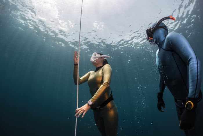 Two lady free diver ascending along the rope in the depth