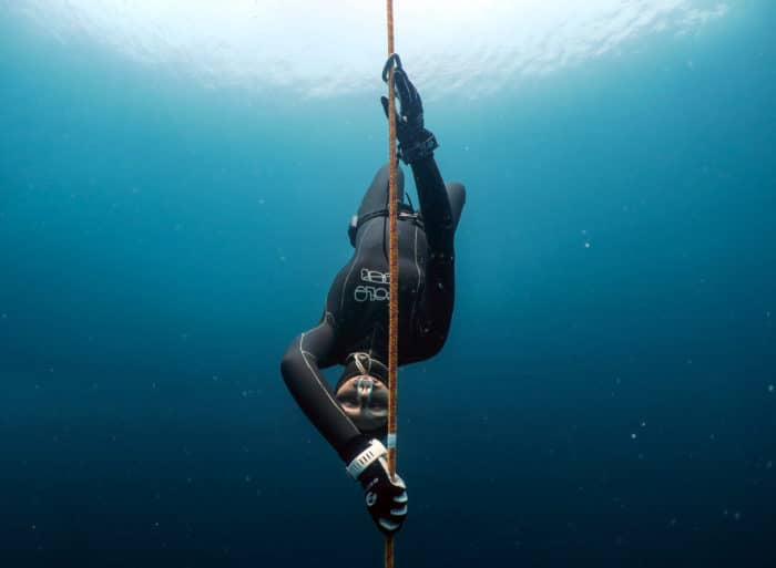 "Freediver descending with a dive computer. Photo by <a href=""https://www.instagram.com/yahiabarakah/"">Yahia Barakah</a>."