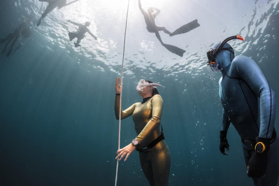 Lady free diver ascending along the rope in the depth