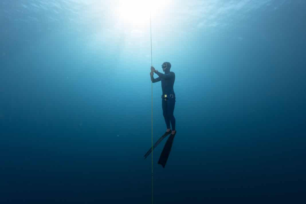 Freediver performing warm up dive - static apnea on the depth