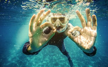Scuba diver underwater showing ok signal with two hands.