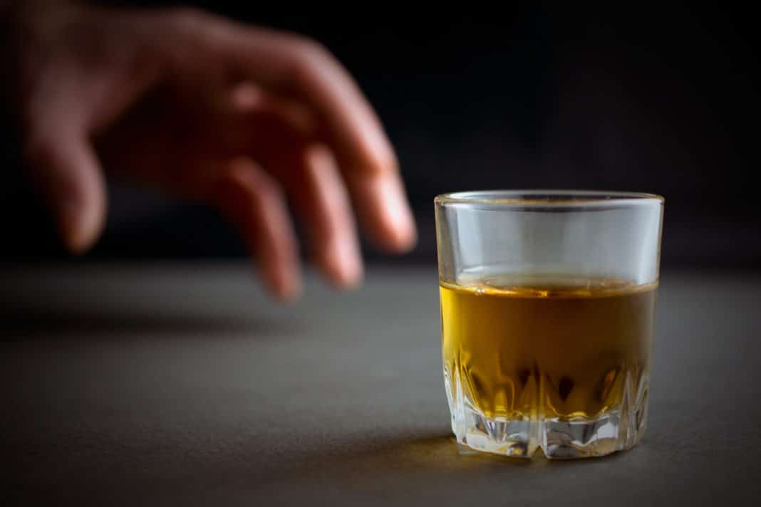hand reaches for a glass of whiskey or cognac or alcohol drink, alcoholism and alcohol abuse concept, defocused, selective focus, close up, gray table, dark background