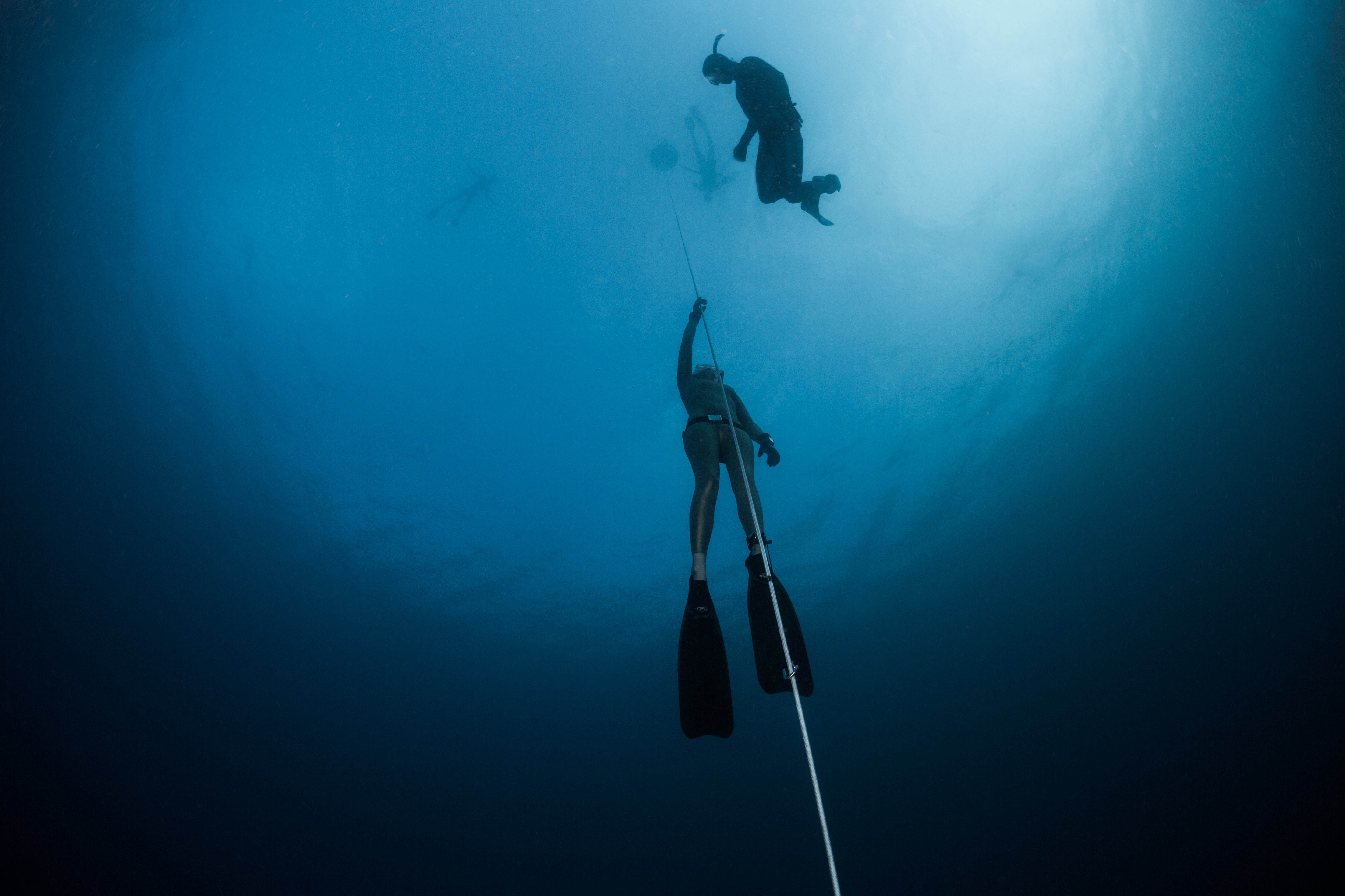 Freediver ascending along the rope in the depth