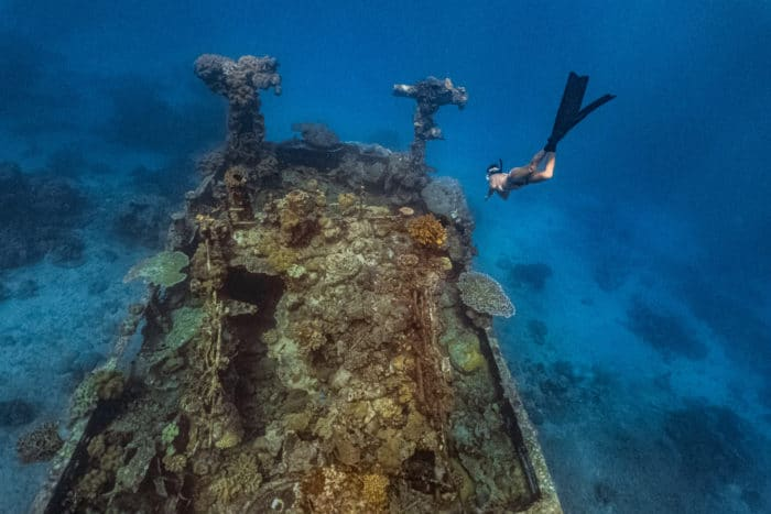 Young female free diver explores a shipwreck in a shallow water in Apo reef, Philippines.