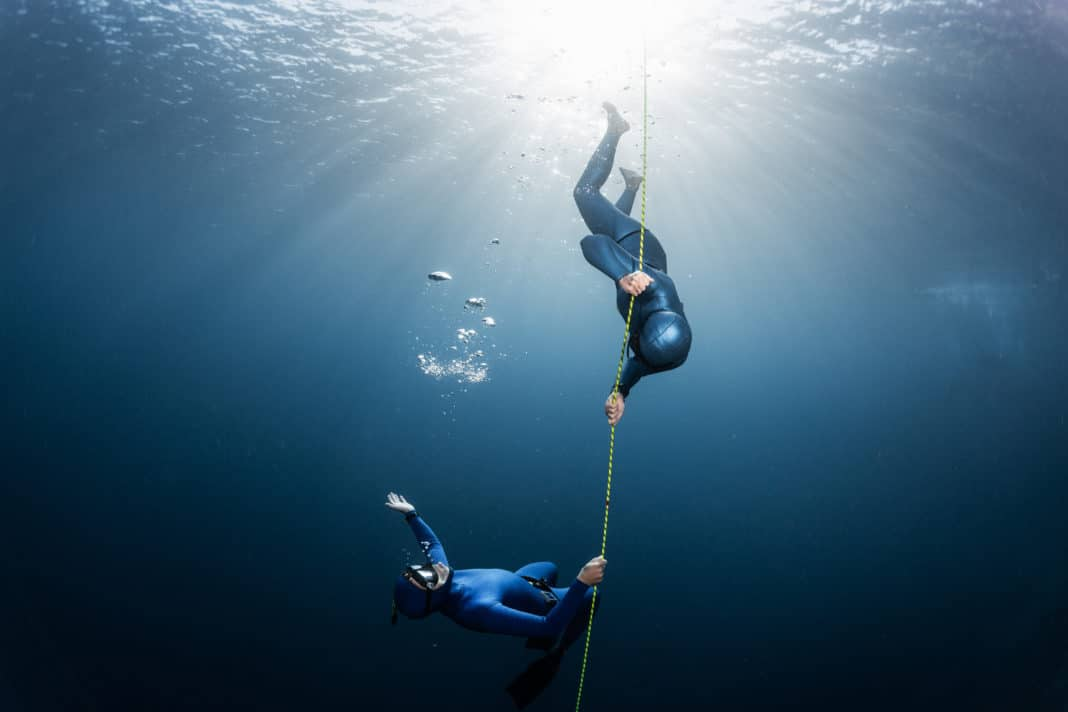 Two freedivers play with bubbles near the rope