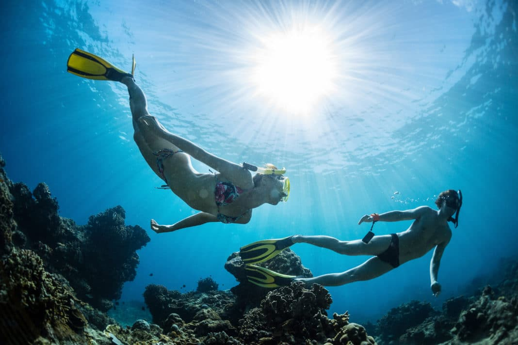 Underwater shot of the couple snorkeling over a coral reef