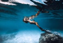 Woman freediver relax over sandy sea with fins. Underwater in blue ocean