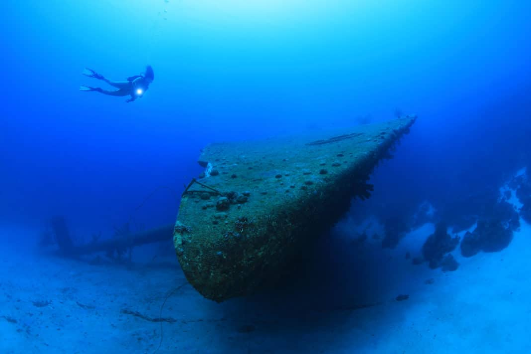 Shipwreck of the Hilma Hooker and scuba diver underwater in the caribbean sea of Bonaire