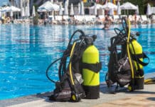 Set of scuba gear set up at the edge of a swimming pool
