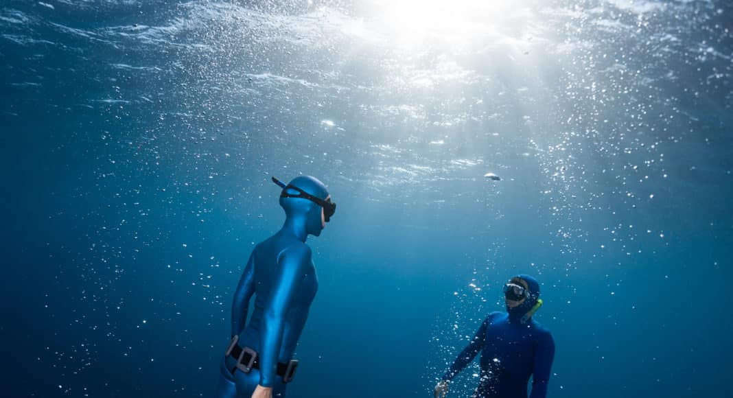 Two freedivers ascending surrounded by bubbles
