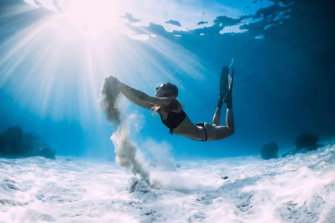 Woman freediver with white sand over sandy sea with fins. Freediving underwater in ocean