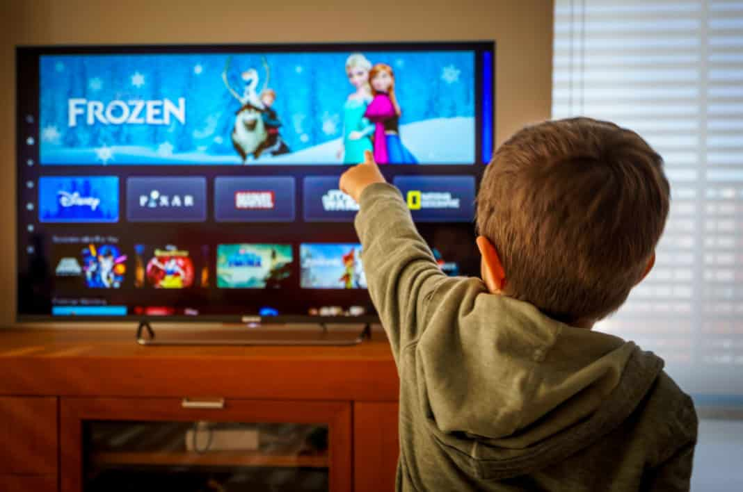 Little boy watching the new Disney plus streaming service and pointing at the TV screen.