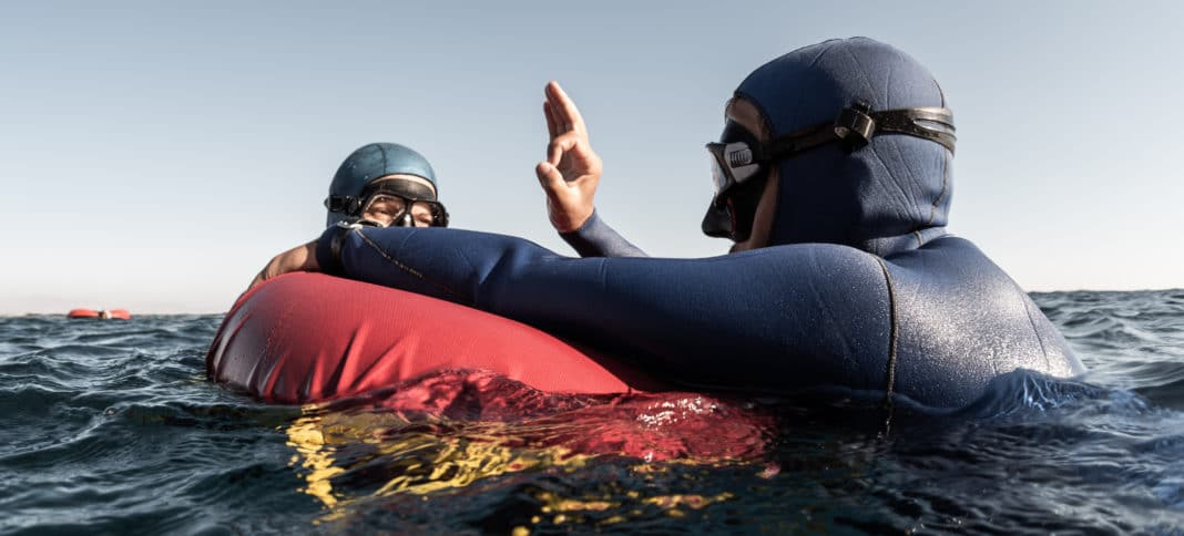 Freediver buddies on surface giving OK signal