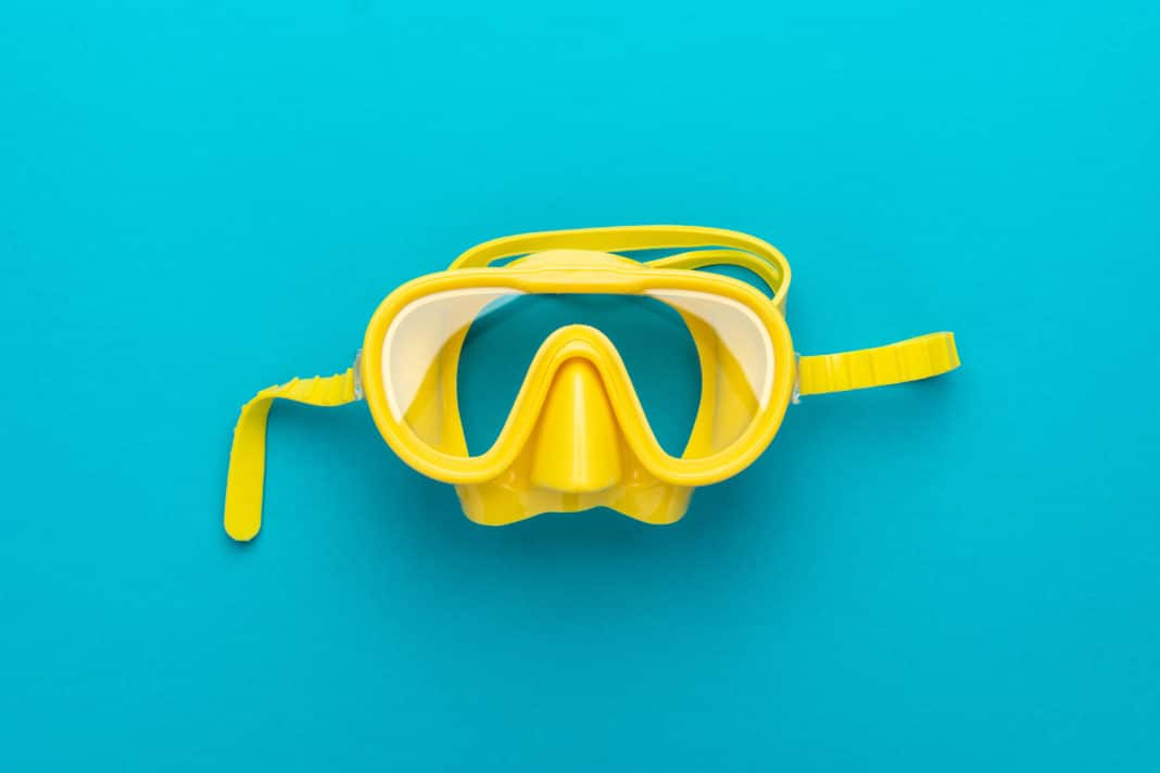 yellow diving mask over blue background