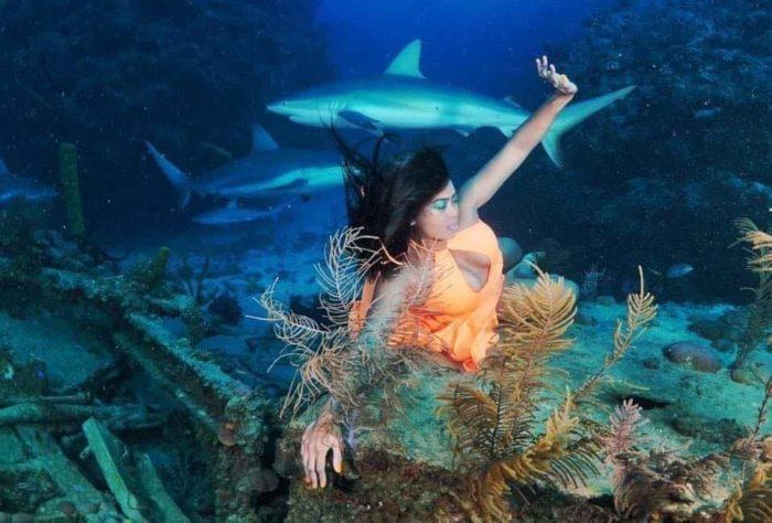Mermaid Odessa posing for an underwater photoshoot for ocean awareness mermaiding freediving
