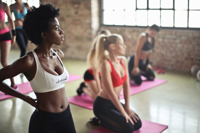 Women training for a yoga class at a gym